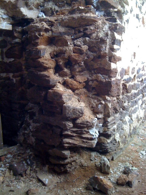 Another basement wall at a broken corner showing some larger stones used to bond across a greater depth