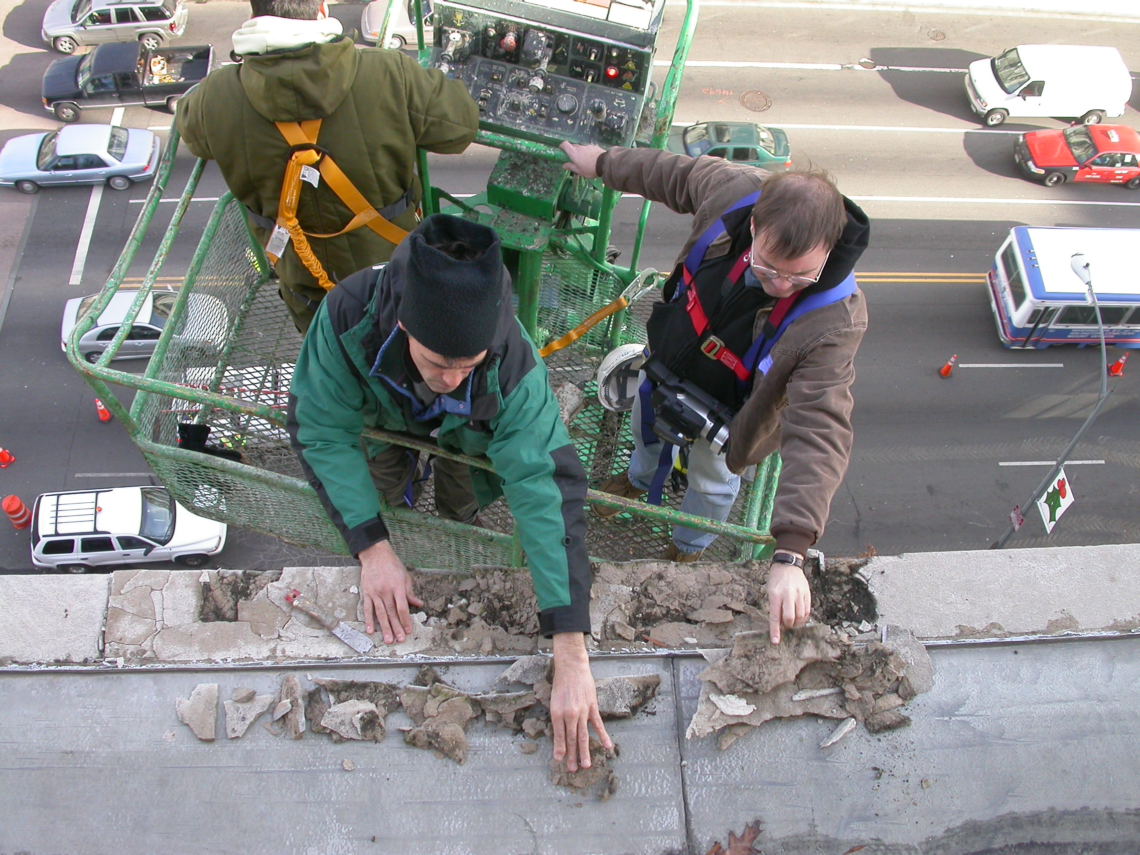Engineer David Wallace and John Greenwalt Lee in 120-foot lift at the Department of Commerce analyzing the causes and developing a solution to failed gutter detailing in 2003.